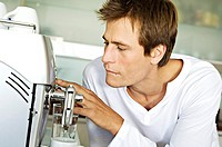 Young man using espresso maker