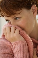 Portrait of young woman covering her mouth with jumper