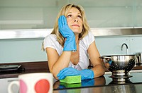 Young woman daydreaming in kitchen