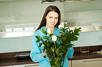 Young smiling woman filling vase with roses