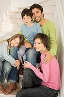 Couple and two children smiling for the camera, sitting on stairs