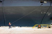 Pearl Harbor, Hawaii (Jun. 26, 2006). A line handler secures mooring lines for the USS Bonhomme Richard. The USS Bonhomme Richard (LHD 6) is pulling i...