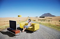 A woman watching television on a couch in the road