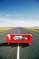 A man sleeping on a couch in the road