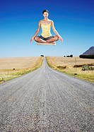 A floating woman doing yoga in the middle of the road