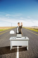 A businessman in the middle of the road at his desk