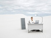 A businessman in the middle of nowhere at his desk