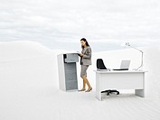 A businesswoman in the middle of nowhere at her filing cabinet