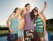 Friends hanging out by a pool taking pictures