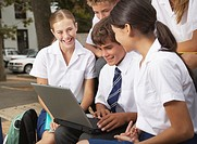 Students outside their school looking at a laptop