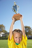 A boy holding up a trophy