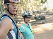 A couple in bike helmets standing outdoors