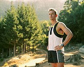 A man in work out gear standing in the woods