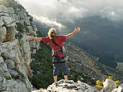 A man with raised arms on top of a mountain