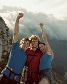 Three mountain climbers with their arms raised in the air