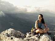 A woman climber sitting on top of a mountain