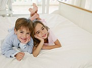 Girl and boy in robe on bed