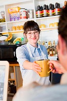 Female store clerk giving a coffee cup to a man and smiling