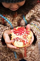 Child holding pomegranate
