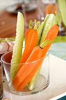 Raw carrots and cucumber sticks in a glass