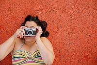 Latino Woman holding a camera.
