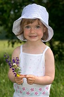 Little Girl Holding Flowers in a Meadow