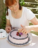 Woman decorating a blueberry cake