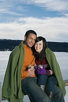 Couple wrapped in blanket and drinking hot cocoa