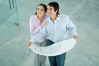 Young couple holding blueprints, smiling
