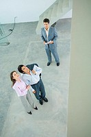 Male real estate agent standing in home interior with young couple, full length, high angle view