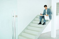 Man sitting on stairs, looking at blueprints