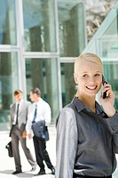 Young businesswoman using cell phone, looking away, associates in background