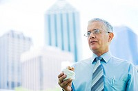 Businessman holding sandwich, office buildings in background
