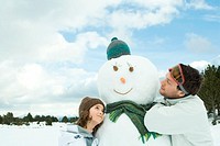 Brother and sister embracing snowman, smiling, head and shoulders