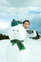 Young man standing behind snowman, pointing, making faces at camera