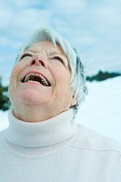 Senior woman laughing with head back in snowy landscape, portrait