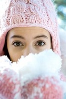 Preteen girl holding handful of snow in mittens, looking at camera