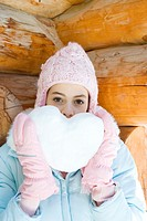 Preteen girl holding up heart made of snow, portrait