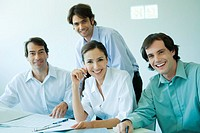 Four business associates smiling at camera, waist up