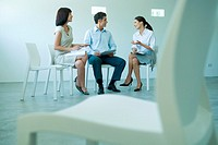 Three business associates sitting in chairs, discussing, full length