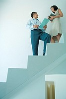 Businessman and young businesswoman standing on stairs, looking at each other, low angle view