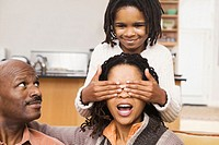 African-American family at home, parents on sofa & daughter covering mother´s eyes with hands from behind. Guess who?