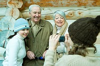 Teenage girl photographing grandparents and sister with digital camera, waist up