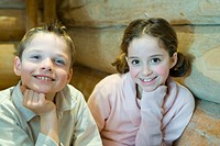 Boy and girl sitting side by side, hand under chin, smiling at camera