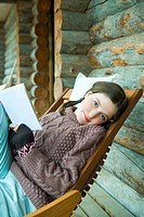 Teenage girl reading book, smiling at camera, dressed in winter clothing