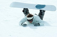 Young snowboarder fallen on the ground, full length