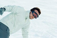Young man bending over in snow, dressed in ski clothing, waist up