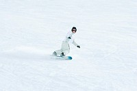 Young snowboarder on ski slope, mid-distance