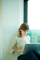 Young woman sitting by window, using laptop