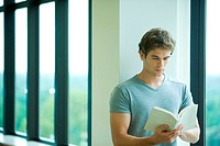 Young man in front of window, reading book